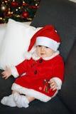 Bambino di Natale con un fondo dell'albero di Natale Fotografia Stock