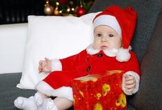 Bambino di Natale con un fondo dell'albero di Natale immagine stock libera da diritti