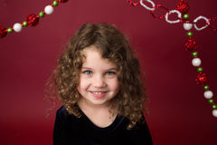 Bambino di Natale: Ragazza felice su fondo rosso Fotografia Stock