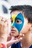 Bambino di nove anni del ragazzo giovane facendo il suo dipingere fronte per divertimento ad una festa di compleanno Immagini Stock Libere da Diritti