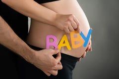 Bambino di parola della tenuta dell'uomo e della donna incinta immagine stock