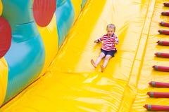 Bambino di quattro anni che gioca su un trampolino Immagine Stock
