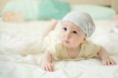Bambino di quattro mesi curioso sul letto Immagini Stock Libere da Diritti