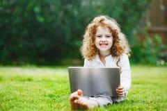 Bambino di risata che lavora con il taccuino che mostra i denti bianchi sani Fotografie Stock Libere da Diritti