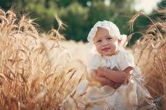 Bambino di risata nel campo di frumento pieno di sole Fotografia Stock