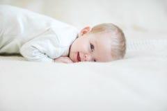 Bambino di risata sul letto Fotografia Stock