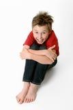 Bambino di seduta in jeans e maglietta Immagini Stock