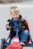 Bambino di smiley sull'automobile del giocattolo con i pedali Fotografie Stock