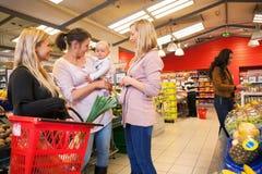 Bambino di trasporto della madre con l'acquisto degli amici Immagine Stock Libera da Diritti