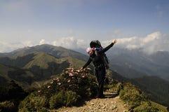 Bambino di trasporto della madre felice in cima alla montagna Immagine Stock