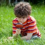 bambino di vetro che ingrandice usando Immagini Stock