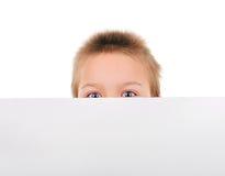 Bambino dietro la carta in bianco fotografia stock libera da diritti