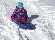 Bambino divertendosi sulla collina della slitta Fotografia Stock