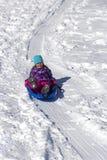 Bambino divertendosi sulla collina della slitta Fotografie Stock