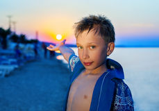 Bambino divertente bello che sta sulla spiaggia al tramonto sulle vacanze estive fotografia stock libera da diritti