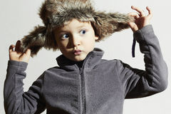 Bambino divertente in cappello di pelliccia I bambini adattano lo stile casuale dell'inverno Little Boy Emozione dei bambini Fotografia Stock Libera da Diritti