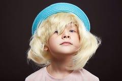 Bambino divertente in cappello ed in parrucca immagine stock