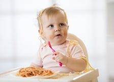 Bambino divertente che mangia tagliatella Il bambino sudicio mangia gli spaghetti con la forcella che si siede sulla tavola a cas immagine stock libera da diritti