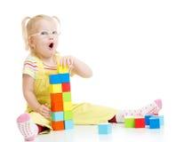 Bambino divertente in eyeglases che fanno torre facendo uso dei blocchi Fotografie Stock Libere da Diritti