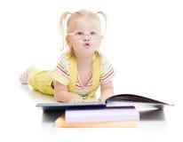 Bambino divertente in libro di lettura di eyeglases isolato Fotografia Stock
