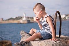 Bambino divertente in occhiali da sole e maglietta giro collo che si siedono sul frangiflutti contro il mare all'estate Fotografia Stock Libera da Diritti