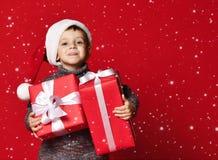 Bambino divertente sorridente in regalo rosso di Natale della tenuta del cappello di Santa a disposizione Concetto di Natale immagine stock libera da diritti