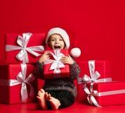 Bambino divertente sorridente in regalo rosso di Natale della tenuta del cappello di Santa a disposizione Concetto di Natale immagine stock