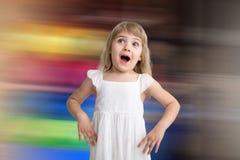 Bambino divertente in vestito bianco che salta e che ride sul fondo colorato Piccola ragazza graziosa su fondo copia fotografie stock libere da diritti