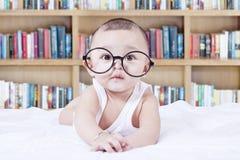 Bambino dolce con i vetri e un fondo dello scaffale Fotografia Stock