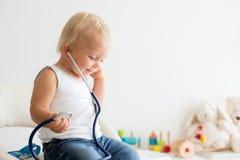 Bambino dolce, neonato, giocante al dottore facendo uso dello stetoscopio al liste fotografie stock libere da diritti