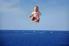 Bambino durante il volo sopra il mare Fotografie Stock