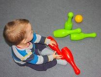 Bambino e bowling Un ragazzino sta sedendosi sul pavimento con la parodia fotografia stock