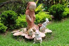 Bambino e conigli di sorriso in un giardino o in un parco Immagine Stock Libera da Diritti