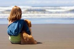 Bambino e cucciolo alla spiaggia Fotografie Stock