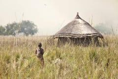 Bambino e grassfire, Sudan del sud Immagine Stock
