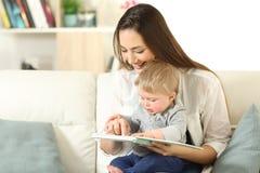 Bambino e madre che leggono insieme un libro fotografie stock
