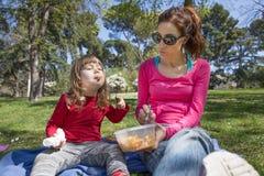 Bambino e madre che mangiano pasta in parco Immagini Stock