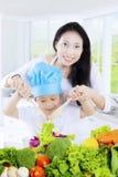 Bambino e madre che mescolano insalata fotografie stock