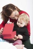 Bambino e mamma che aprono scatola rossa Fotografia Stock Libera da Diritti