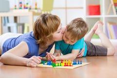 Bambino e mamma della famiglia che giocano gioco da tavolo a casa sul pavimento a casa Immagine Stock