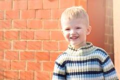 Bambino e muro di mattoni sorridenti fotografie stock libere da diritti