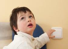 Bambino e un interruttore chiaro Fotografie Stock Libere da Diritti