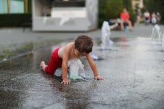 Bambino e una fontana di spruzzatura Immagini Stock Libere da Diritti