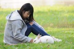 Bambino ed il suo animale domestico Bunny Playing Outdoors Fotografia Stock
