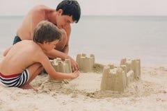 Bambino ed il suo castello di sabbia della costruzione del padre Fotografie Stock Libere da Diritti