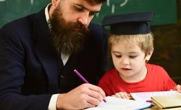 Bambino entusiasta che studia con l'insegnante Concetto di Homeschooling Insegnante nell'usura convenzionale ed in allievo in toc Fotografia Stock Libera da Diritti
