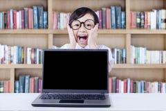 Bambino espressivo con il computer portatile che grida nella biblioteca Fotografia Stock Libera da Diritti
