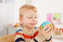 Bambino in età prescolare con il globo nell'aula Immagini Stock Libere da Diritti