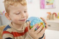 Bambino in età prescolare con il globo nell'aula Fotografia Stock