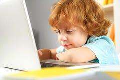 Bambino in età prescolare concentrato che studia con l'aiuto delle nuove tecnologie Immagine Stock